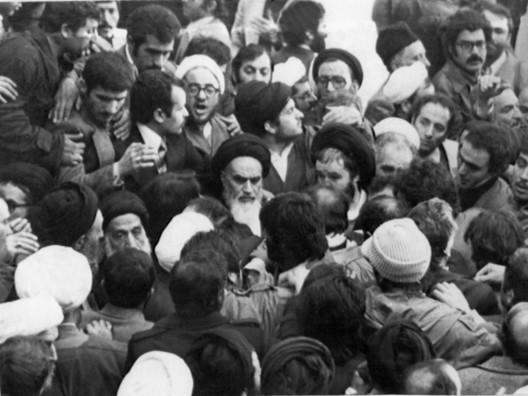 El principal líder de la oposición, el Ayatolá Jomeini (centro), es protegido de la multitud entusiasta a su regreso del exilio