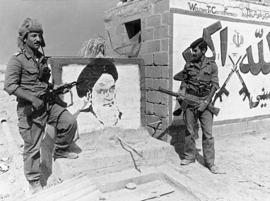 Soldados iraquíes adentrados en territorio iraní posan junto a un retrato del Ayatolá Jomeini pintado en la pared de un puesto policial