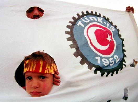 Niño asomado a través de una pancarta de la Confederación Sindical Turca (Türk-is)