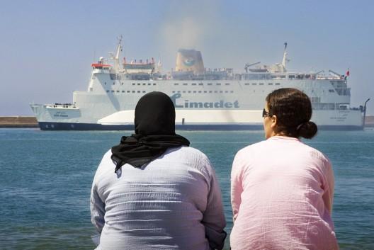 Dos mujeres observan cómo zarpa un ferry del puerto de Almería