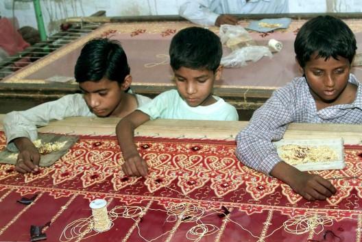 Niños paquistaníes se afanan para confeccionar un vestido de novia en un taller