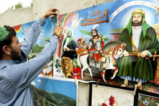 Un vendedor ambulante coloca pósters con los retratos de héroes musulmanes