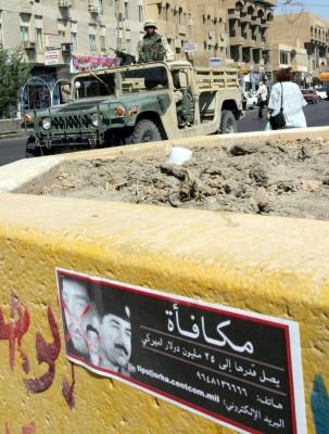 Una patrulla del ejército de los Estados Unidos pasa cerca de un póster de Saddam Husein en el que se ofrece una recompensa de 25 millones de dólares a quien proporcione información sobre su paradero