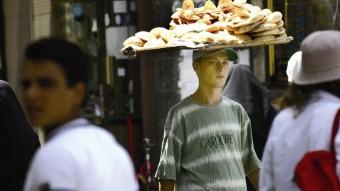 Un joven lleva una bandeja con el tradicional pan árabe en el zoco de Al Hamidiya, uno de los más antiguos del mundo árabe