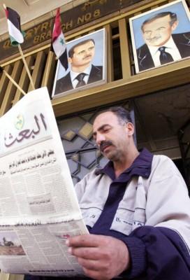 """Un vigilante lee el periódico oficial """"al-Baaz"""" franqueado por los retratos del actual presidente sirio"""
