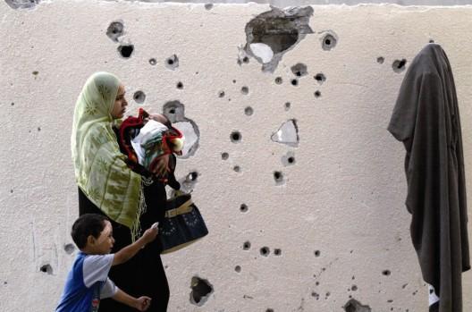Una mujer palestina y sus hijos pasan frente a un muro agujereado por armas de fuego