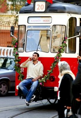 Un joven viaja sentado en el tope de un tranvía de estilo antiguo