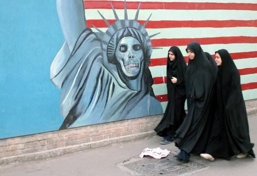 Jóvenes iraníes pasean ante un mural antiamericano en su camino para atender una concentración en conmemoración del 24 aniversario de la ocupación de la embajada de Estados Unidos