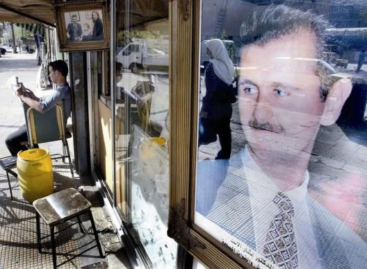 Reflejo de una mujer siria en el retrato del presidente sirio Bashar al-Assad en el escaparate de una tienda