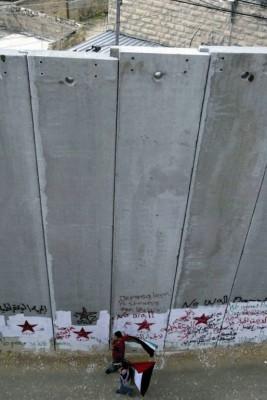 Manifestantes con banderas palestinas cerca del muro construido por el gobierno de Israel alrededor de los territorios palestinos