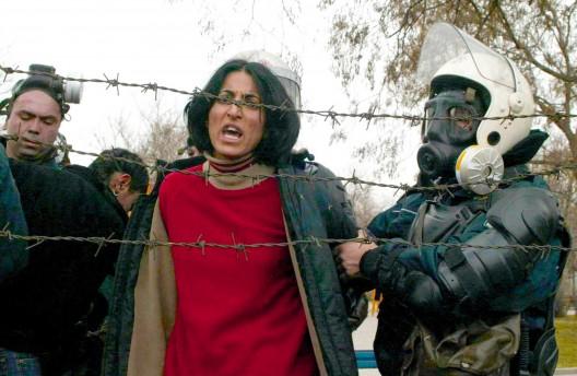 Policías antidisturbios detienen a una estudiante durante una manifestación