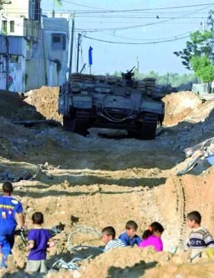 Niños palestinos juegan cerca de un tanque israelí