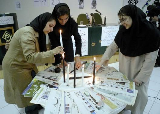 Tres periodistas encienden velas como símbolo de duelo por la censura de los medios durante una protesta en la sede de la Asociación Iraní de Prensa