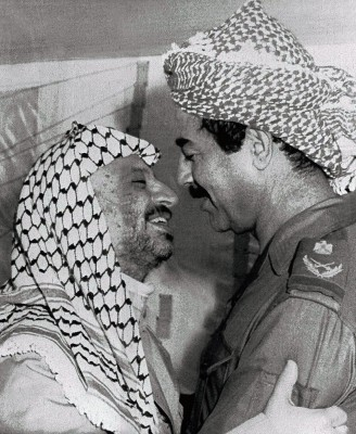 El presidente palestino Yasir Arafat, entonces líder de la OLP, saluda al presidente iraquí Saddam Husein