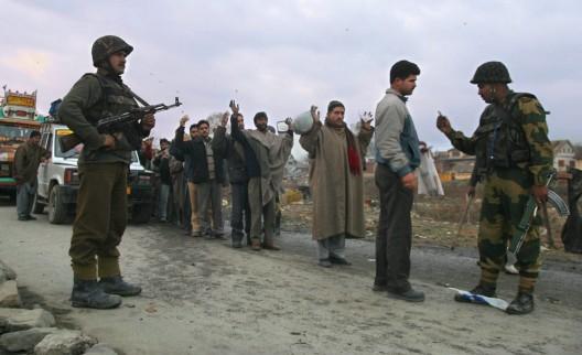 Un oficial de aduanas indio examina el pasaporte de un musulmán de Kachemira mientras otros esperan su turno para pasar la frontera india