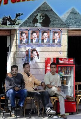 """Jóvenes egipcios en el """"Café Pirámides"""" bajo unos carteles electorales durante la celebración de la segunda vuelta de la primera ronda de las elecciones parlamentarias"""