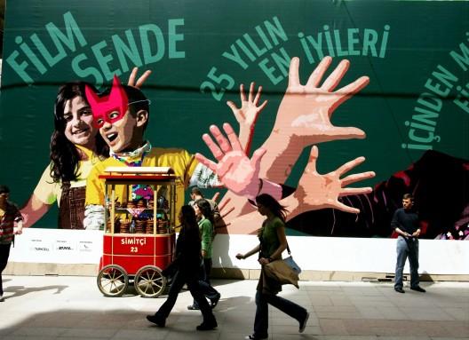 Transeúntes caminan junto a un mural gigante situado en la principal calle peatonal del centro de Estambul