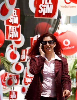 Una mujer habla por el móvil al llegar al acto de compra del operador turco de telefonía móvil Telsim por parte de Vodafone