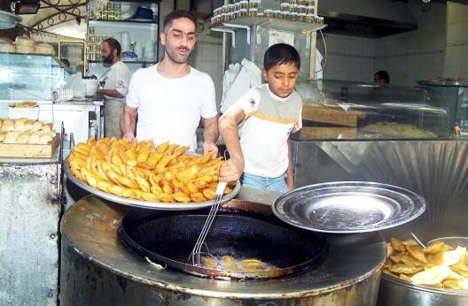 Dos vendedores preparan qatayef, típico dulce de Damasco