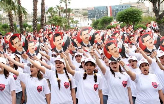 Cientos de personas muestran retratos del presidente sirio, Bashar al-Asad
