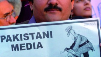 Un periodista sostiene una pancarta contra la censura a los medios