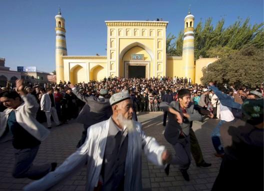 Musulmanes uigures danzan a las puertas de la mezquita Idhka