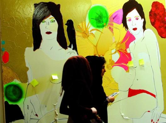 Dos asistentes a la feria Art Dubai pasan junto a una obra de la Galería Caprice Horn de Berlín