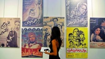 Una mujer observa carteles de películas egipcias como parte de los actos en conmemoración del Centenario de la Industria Fílmica Egipcia