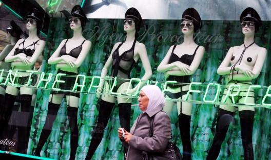 Una mujer musulmana pasa junto al escaparate de una tienda erótica