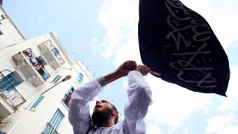 Un manifestante ondea una bandera con la shahada (profesión de fe islámica)