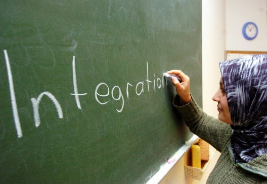 """Una mujer turca escribe la palabra """"integración"""" en un aula"""