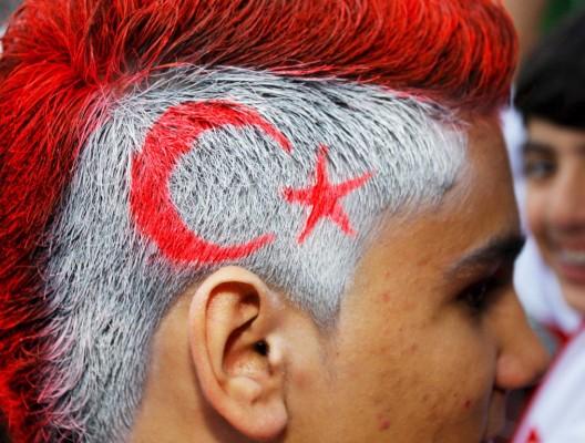 Un seguidor turco, con el pelo decorado con motivos nacionales