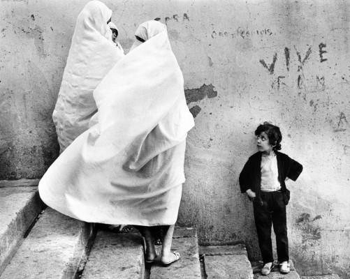 Una niña contempla a varias mujeres vestidas de manera tradicional
