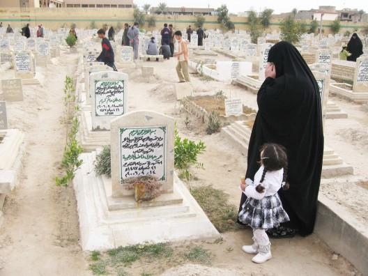Una anciana y una niña visitan la tumba de familiares
