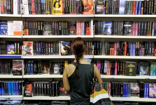 Una mujer observa una gran estantería con libros